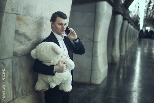 Man is talking on the phone, in his hands a teddy bear is a toy.