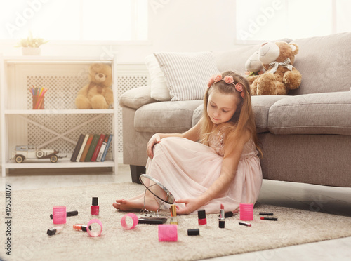 Little girl doing make up with mom`s cosmetics