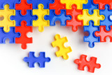 Pieces from a colorful jigsaw puzzle arranged to form a page on white background. Break barriers together for autism concept - 195331413