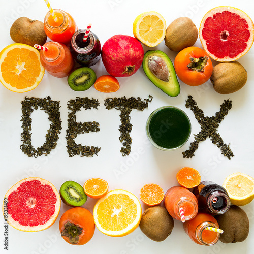 Healthy eating concept. Word 'detox' from green tea with colorful smoothies and fruits. Top view
