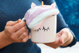 Mug in woman hands with colorful cream - 195334671