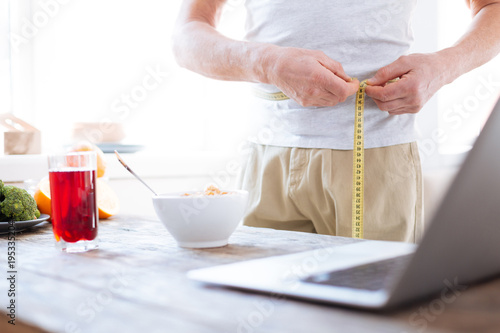 Ideal waist. Close up of male hands using metre ruler while white bowl and advanced laptop standing on wooden surface
