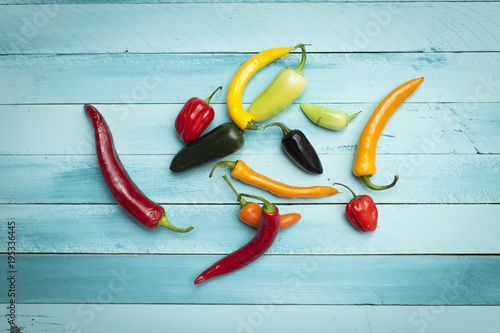 Fotobehang Hot chili peppers different colorful chili peppers on a turquoise wooden background.