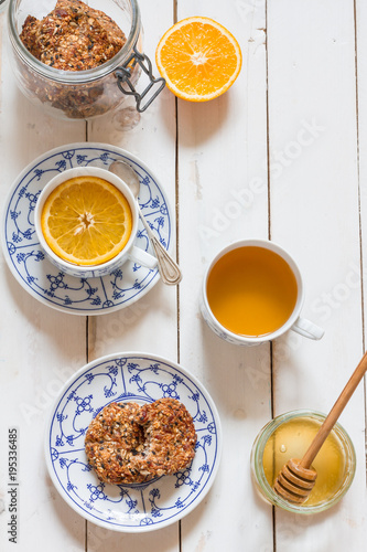 Dates and coconut cookies. Green tea with orange in white and blue cup. White wooden plate. Flatlay.