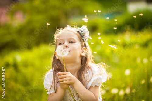 Small girl blowing dandelion