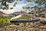 Glenfinnan Railway Viaduct in Scotland with the Jacobite steam train against sunset over lake - 195347297