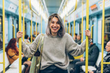 waist up young woman travelling underground looking camera smiling - traveller, commuter, happiness concept - 195356037