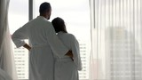 Young couple in bathrobe unveil curtains  - 195356055