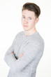 Portrait of smart serious young man standing against grey white background