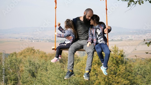 Portrait of dad swinging with daughters on a swing under a tree.