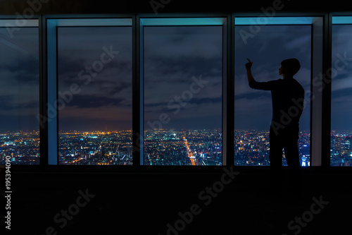 Man looking out large windows high above a sprawling city at night - 195394090