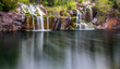 Long exposure waterfall over rocks with reflections in water - 195410266
