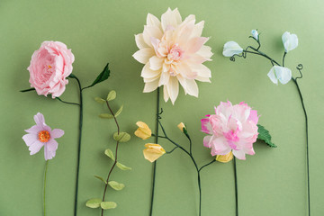 Crepe paper flowers dahlia, cosmos peony, sweet peas and eucalyptus on green background