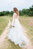 bride in white llight wedding dress with bridal bouquet walking in lane, back view