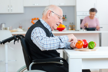 senior couple cooking together - man disabled on wheelchair