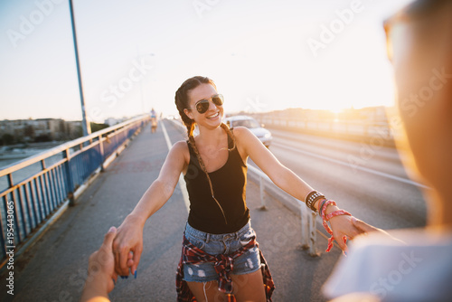 Poster Cute girl holding both hands with a boyfriend enjoying summer while crossing the bridge.