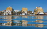 Spain Costa Brava seaside town with apartment buildings on the waterfront seen from water surface, Mediterranean sea, Santa Margarida, Roses, Catalonia, Girona - 195448201