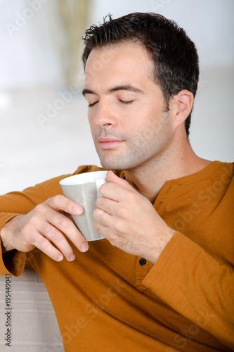 Fototapeta young man enjoying tea with closed eyes