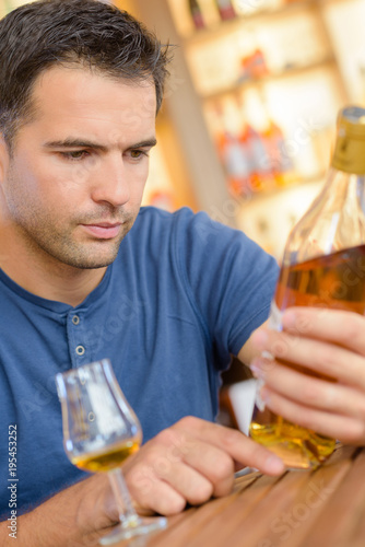 Man reading label on bottle of brandy