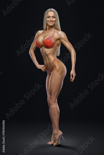 Image inspire concept champion female fitness bikini model competition Confident attractive happy young bodybuilder looking forward Sports slim body perfect shape Black background Red swimsuit