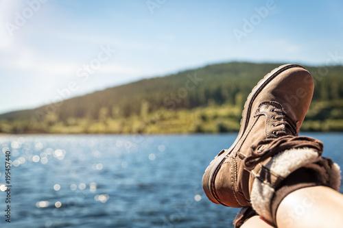 Konzept Erholung und Wandern, Wanderschuhe und ein See mit Wald