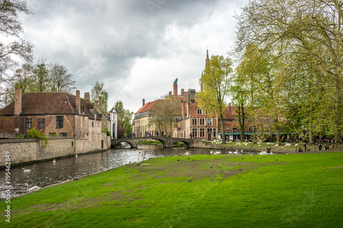 Fotobehang Brugge Bruges (Brugge) canal with swan at bridge and gate to Beguinage (Prinselijke Begijnhof van Wijngaerde)