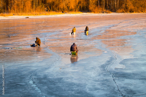 Tuinposter Natuur A man on ice is fishing in the evening