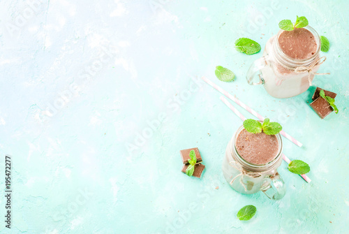 Poster Milkshake Chocolate smoothie or milkshake with mint and straw, in mason jar on light blue background, copy space top view