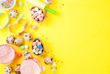 Sweet baking concept for Easter, cooking background with baking - with a rolling pin, whisk for whipping, cookie cutters, quail eggs, sugar sprinkling. Bright yellow background, top view copy space - 195472651