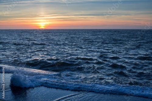 Fotobehang Strand Waterfront ocean surf during amazing sunset.