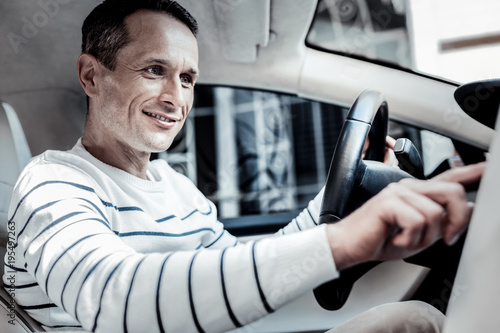 Smart system. Positive joyful good looking man sitting in his car and smiling while pressing a button