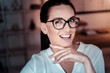 Tell me something. Joyful pretty bespectacled woman being in the empty room smiling and holding head near chin.