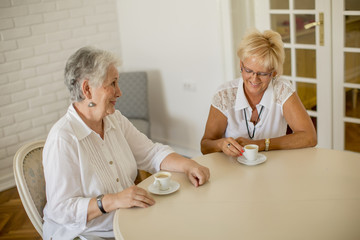 Two older women drinking coffe at home and talking
