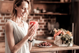 Absolutely healthy. Delighted attractive nice woman looking at the pepper and smiling while enjoying healthy food - 195506443
