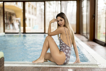 Young woman relaxing by pool side