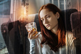 Depressed woman. Young depressed woman sitting in an armchair and looking at the glass with alcohol while being home alone and feeling depressed - 195511673