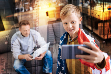 Taking photos. Attentive concentrated smiling boy standing with a big American flag on his shoulders and holding a modern smartphone while taking a photo with his serious calm father