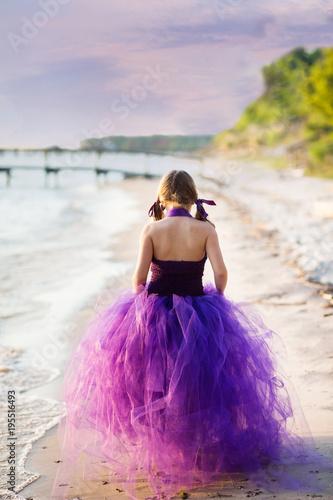 Fotobehang Strand Little Girl in Purple Dress Walking on Beach at Sunset