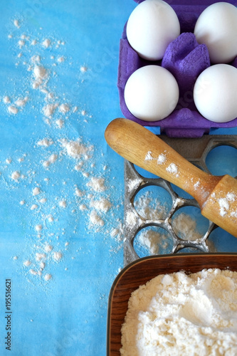 Fototapeta Eggs, flour and kitchen utensils for cooking homemade dumplings on blue background