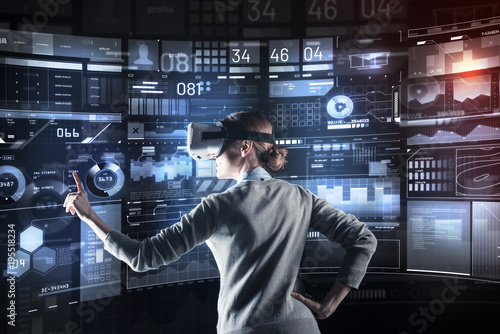Excellent. Calm attentive cheerful programmer looking careful and pointing to the screen while working in convenient virtual reality glasses
