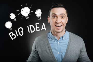 Big idea. Emotional enthusiastic young employee feeling excited and smiling happily while getting a brilliant idea connected with his new project