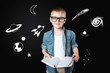 Curious boy. Clever cheerful curious boy wearing big glasses and feeling glad while holding a big notebook and reading the information about the space
