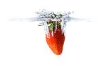 Strawberry splashing into crystal water