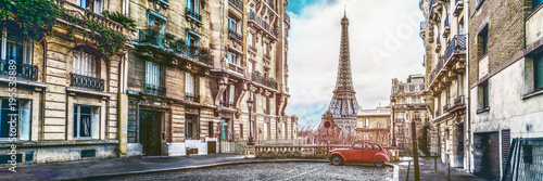 Leinwanddruck Bild The eiffel tower in Paris from a tiny street with vintage red 2cv car