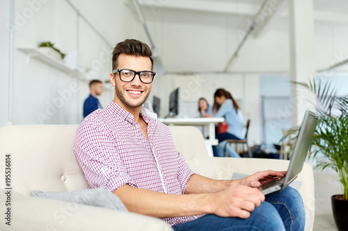 man in eyeglasses with laptop working at office