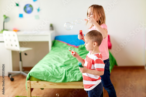 kids blowing soap bubbles and playing at home