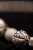 A part of a white bead necklace with gold and silver elements