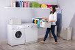 Woman Standing Near Washing Machine With Basket Of Clothes