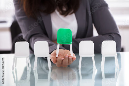 Papiers peints Kiev Businesswoman Choosing Green Chair Among White Chairs In A Row