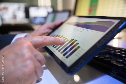 Businessperson Looking At Financial Graph On Digital Tablet
